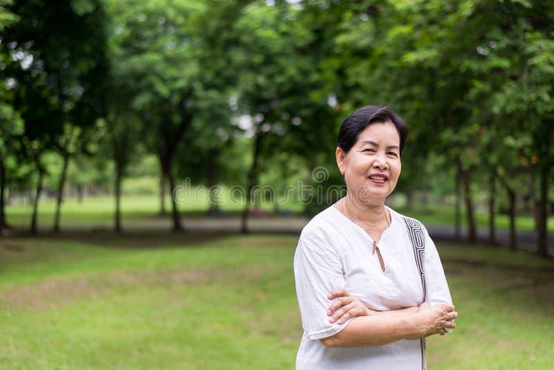 Ritratto della condizione asiatica anziana della donna e delle armi trasversali al parco, felice e sorridendo, pensiero di attegg fotografia stock