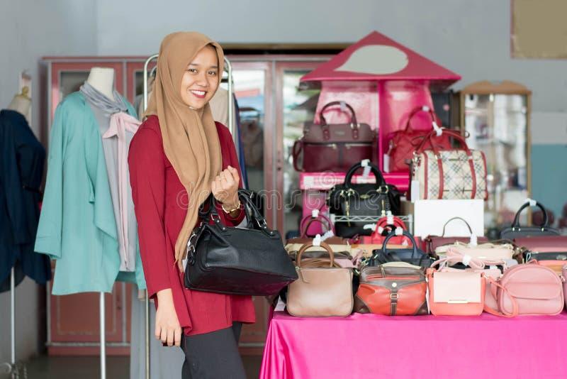 Ritratto della condizione femminile del proprietario e del costume del hijab asiatico con la borsa nera nel suo deposito di modo  fotografia stock libera da diritti