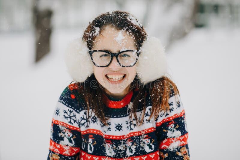 Ritratto della cuffia d'uso della giovane bella ragazza, maglione di inverno che posa nel parco nevoso Donna che guarda macchina  fotografia stock