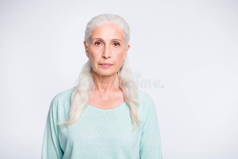 Ritratto della donna affascinante concentrata che sembra il pullover d'uso dell'alzavola isolato sopra fondo bianco immagini stock libere da diritti