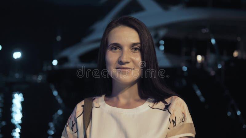 Ritratto della donna alla moda del viaggiatore di estate all'aperto in città europea, baia di notte con gli yacht sui precedenti immagini stock libere da diritti
