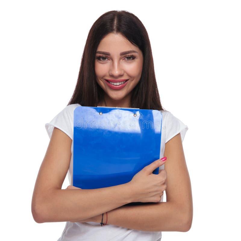 Ritratto della donna allegra castana che tiene una lavagna per appunti blu fotografia stock