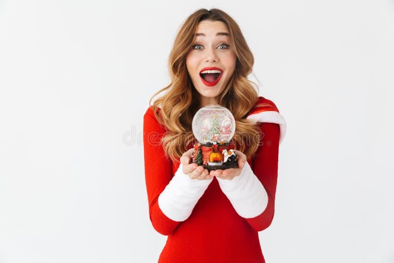 Ritratto della donna allegra 20s che porta il costume rosso di Santa Claus che sorride e che tiene la palla della neve di Natale, fotografia stock