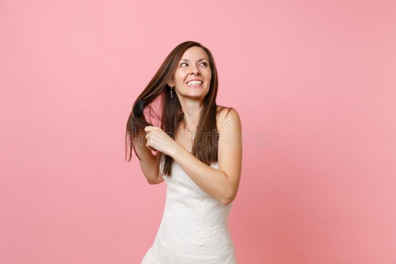 Ritratto della donna allegra sorridente della sposa in bello pettine bianco della tenuta del vestito da sposa, pettinante i suoi  immagine stock libera da diritti