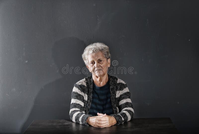 Ritratto della donna anziana povera che si siede alla tavola sul fondo scuro immagini stock