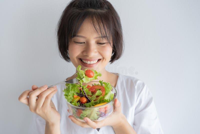 Ritratto della donna asiatica che sorride e che mangia insalata sul concetto sano e di stile di vita bianco del fondo, fotografie stock