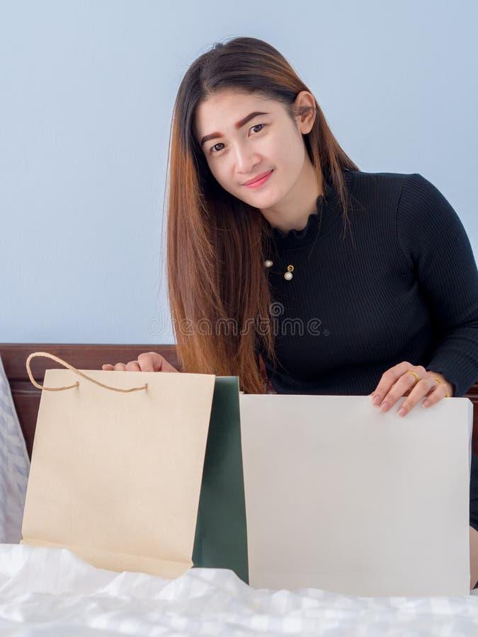 Ritratto della donna asiatica in vestito nero, sul suo letto, affare un concetto decorativo della camera da letto fotografia stock