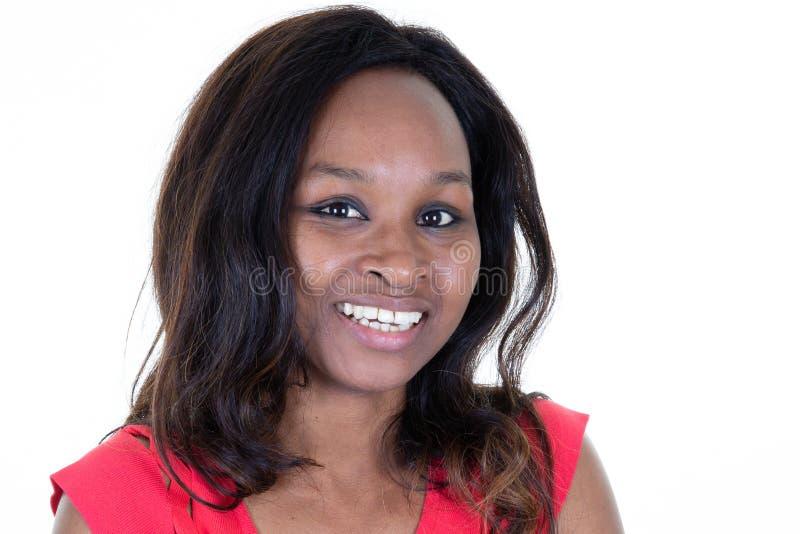 Ritratto della donna attraente afroamericana che sorride contro il fondo bianco fotografia stock
