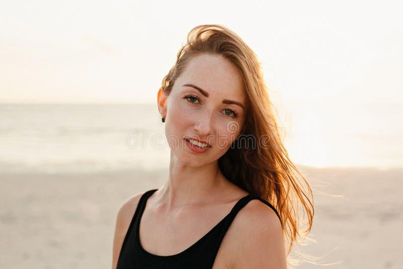 ritratto della donna attraente che esamina macchina fotografica sulla spiaggia dell'oceano immagini stock libere da diritti