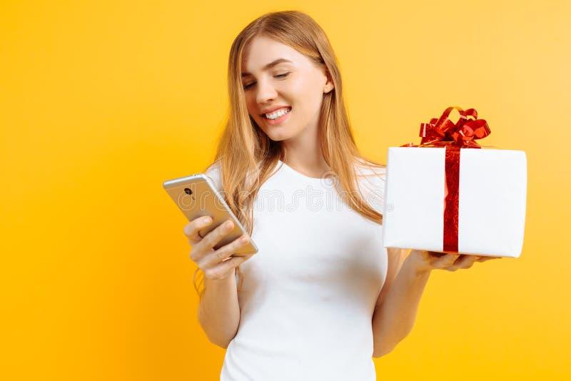 Ritratto della donna attraente sorridente, tenendo il contenitore di regalo, stando e per mezzo del telefono cellulare, isolato s fotografia stock libera da diritti