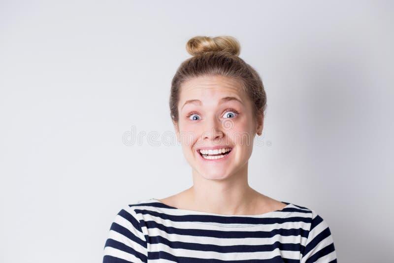 Ritratto della donna bionda di risata e sorridente allegra divertente in vestito a strisce su fondo bianco con lo spazio della co fotografie stock libere da diritti