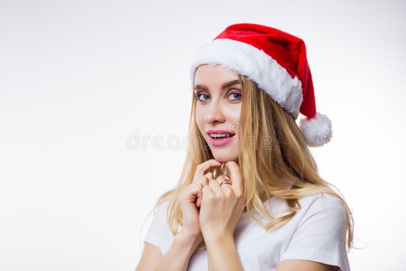 Ritratto della donna bionda sorpresa in cappello rosso di Santa su fondo bianco con lo spazio della copia Emozioni positive, gioi immagine stock