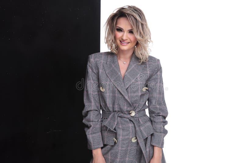 Ritratto della donna bionda sorridente che indossa un vestito grigio di checkerd fotografie stock