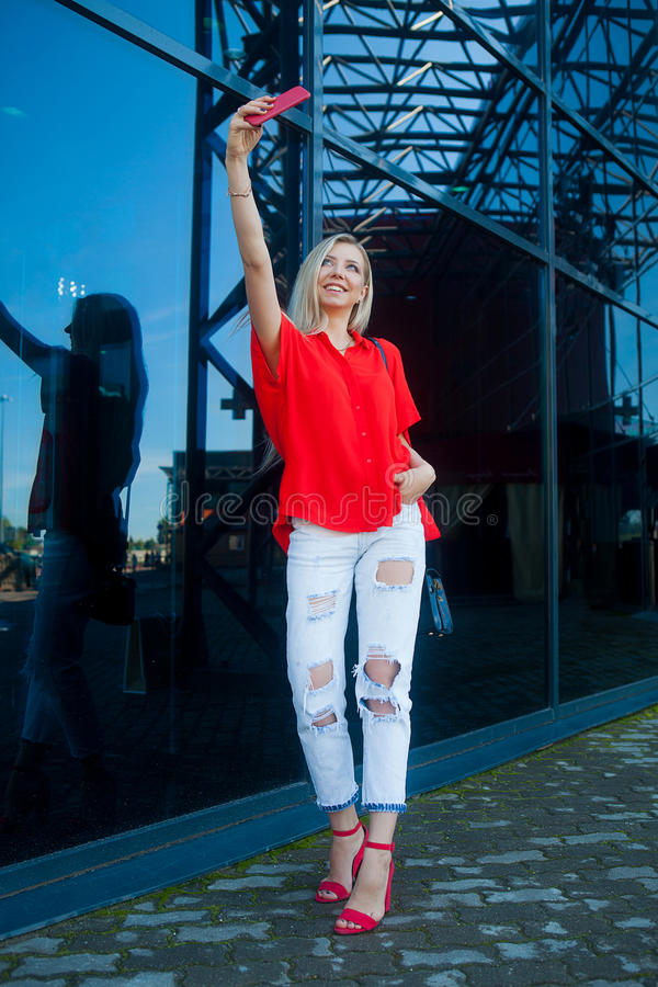 Ritratto della donna bionda sorridente di bellezza in camicia rossa con lo smartphone vicino all'ufficio Fabbricazione del selfie immagini stock libere da diritti