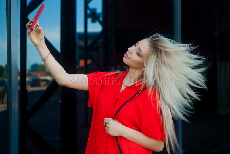 Ritratto della donna bionda sorridente di bellezza in camicia rossa con lo smartphone vicino all'ufficio Fabbricazione del selfie fotografia stock libera da diritti