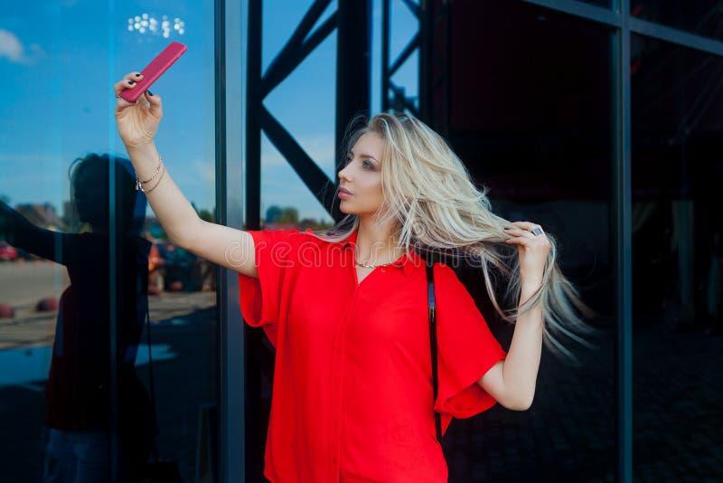 Ritratto della donna bionda sorridente di bellezza in camicia rossa con lo smartphone vicino all'ufficio Fabbricazione del selfie immagine stock