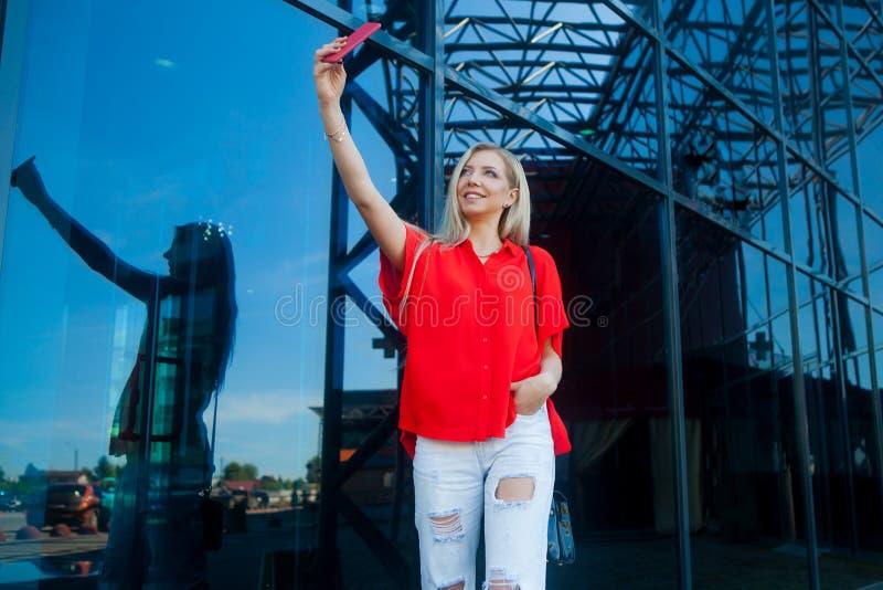 Ritratto della donna bionda sorridente di bellezza in camicia rossa con lo smartphone vicino all'ufficio Fabbricazione del selfie fotografia stock
