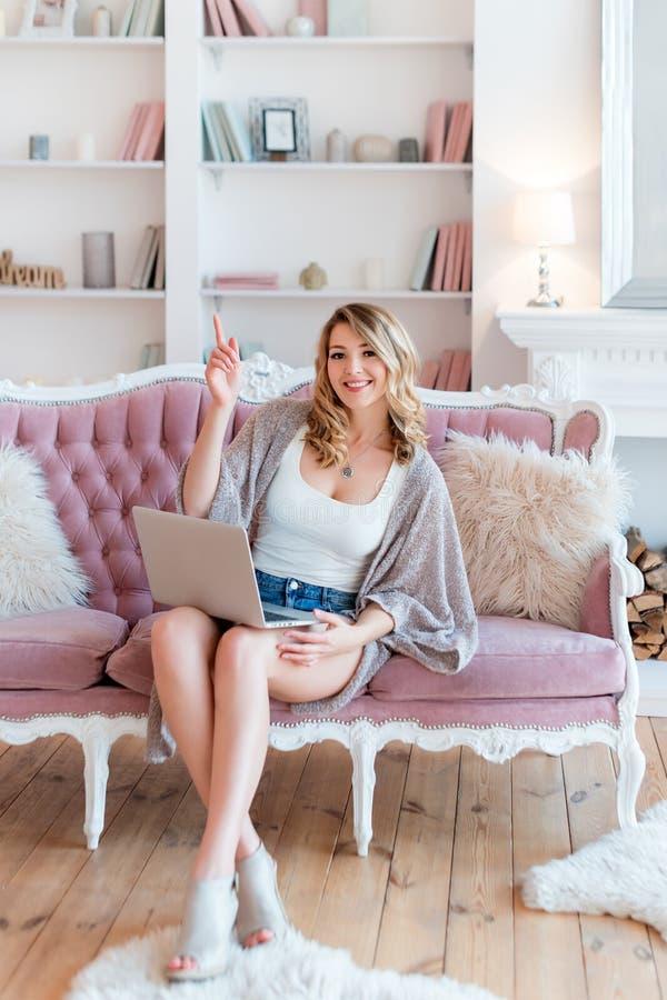 Ritratto della donna bionda splendida con funzionamento del computer portatile a casa Conversazione femminile delle belle free la immagine stock libera da diritti
