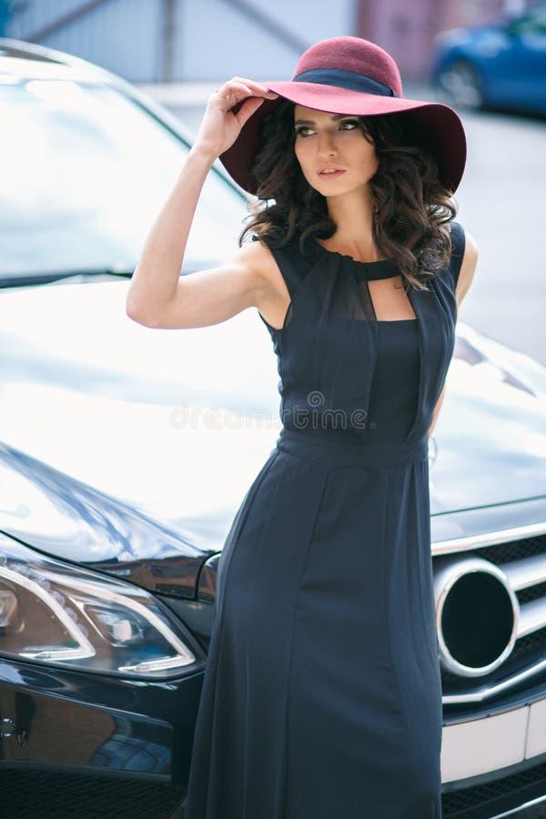 Ritratto della donna castana elegante splendida in un cappello vicino all'automobile nera fotografia stock