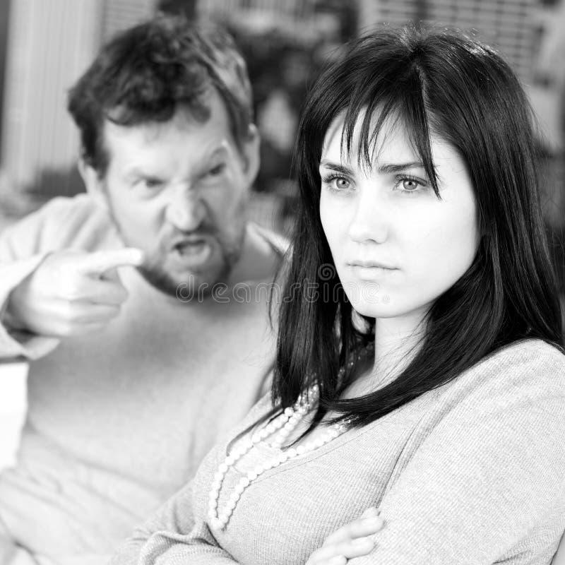 Ritratto della donna che è urlato dal marito a casa in bianco e nero fotografia stock libera da diritti