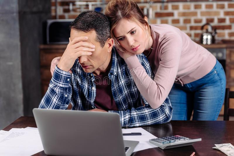 ritratto della donna che abbraccia marito turbato che sedendosi alla tavola con il computer portatile a casa finanziario fotografia stock libera da diritti