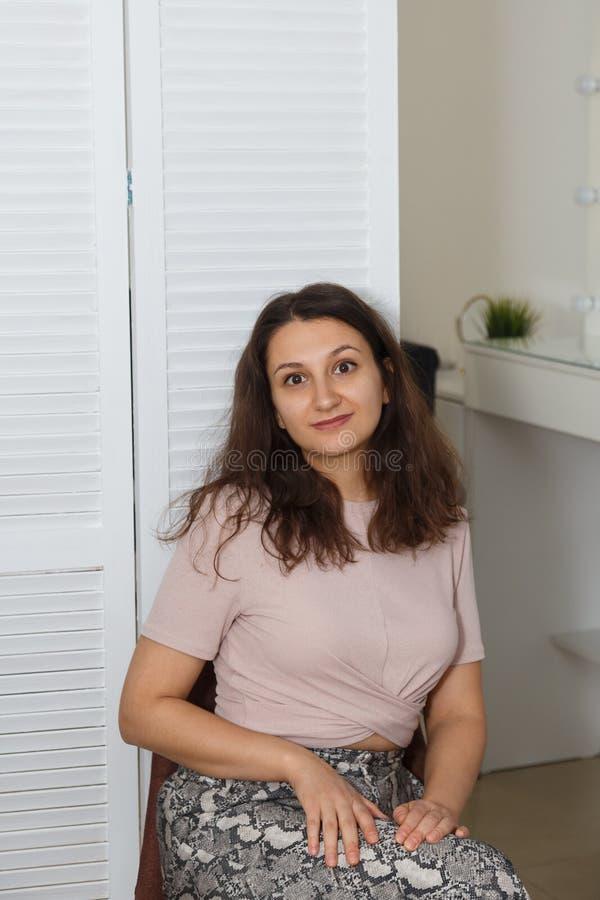 Ritratto della donna che asciuga col phon i suoi capelli al salone di bellezza immagine stock libera da diritti