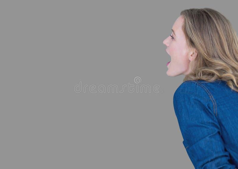 Ritratto della donna che grida con il fondo grigio immagine stock libera da diritti