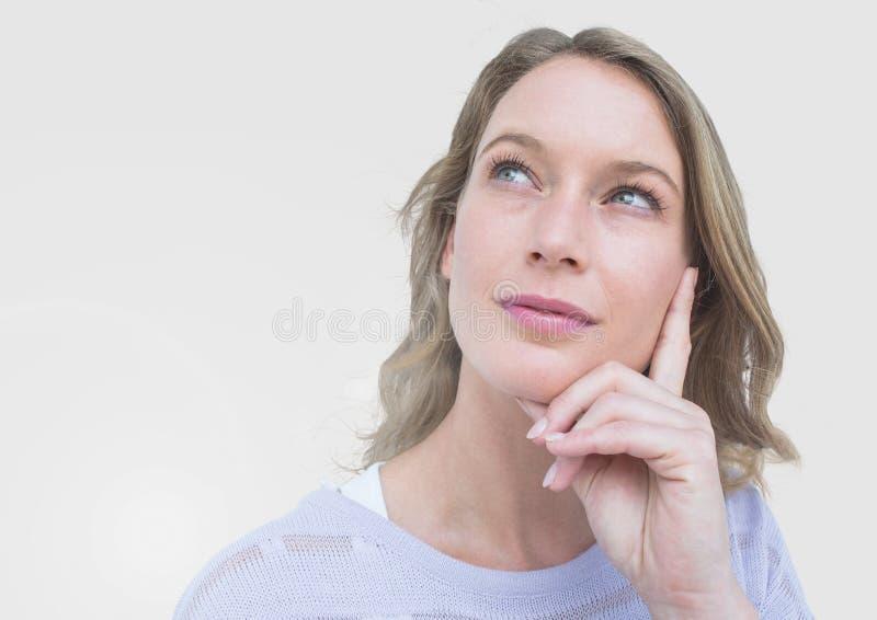 Ritratto della donna che pensa con il fondo grigio fotografie stock libere da diritti