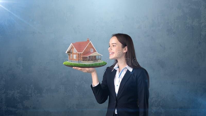 Ritratto della donna che tiene casa di legno rustica sulla palma aperta della mano, sopra il fondo isolato dello studio Concetto  fotografie stock