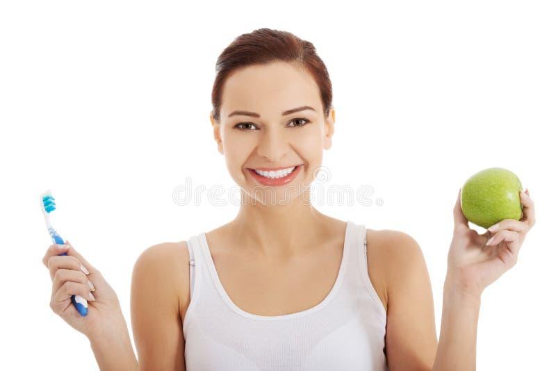 Ritratto della donna che tiene una mela e uno spazzolino da denti fotografie stock