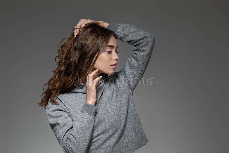 Ritratto della donna con capelli lunghi in maglione grigio fotografie stock