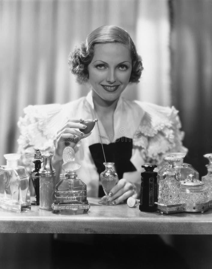 Ritratto della donna con le bottiglie di profumo (tutte le persone rappresentate non sono vivente più lungo e nessuna proprietà e fotografie stock libere da diritti