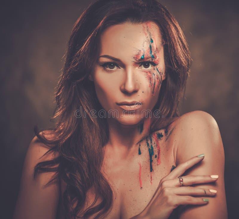 Ritratto della donna con trucco colorato creativo su un fondo scuro immagine stock