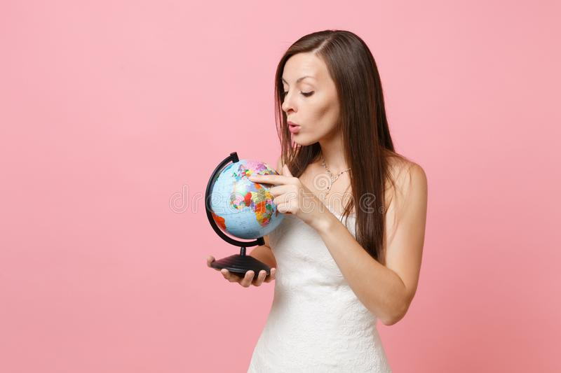 Ritratto della donna curiosa della sposa in vestito da sposa bianco dal pizzo che indica il dito indice sul globo del mondo, sceg immagini stock libere da diritti