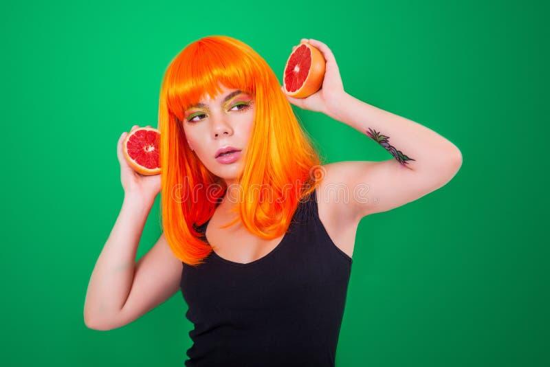 Ritratto della donna dai capelli rossi con pompelmi in primo piano dello studio fotografia stock libera da diritti
