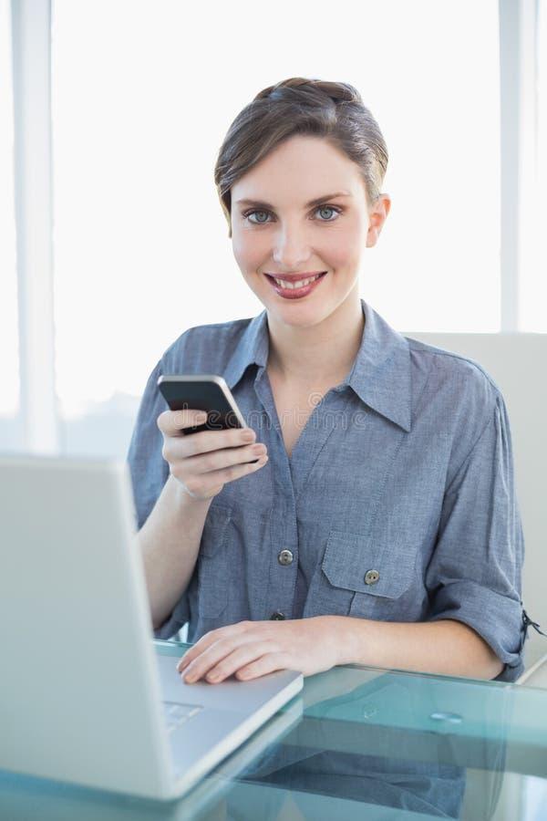 Ritratto della donna di affari abbastanza calma che tiene il suo smartphone che si siede al suo scrittorio immagini stock