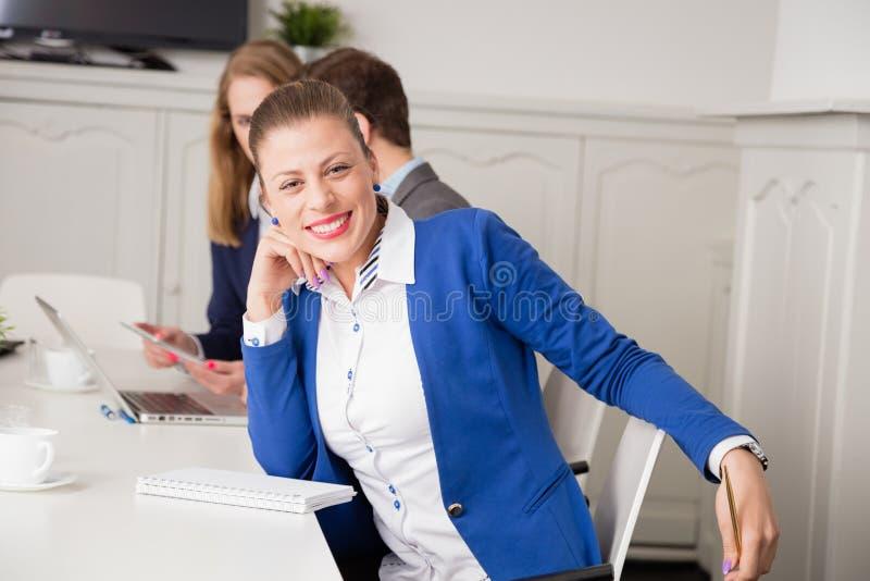 Ritratto della donna di affari allo scrittorio nel corso della riunione immagine stock libera da diritti
