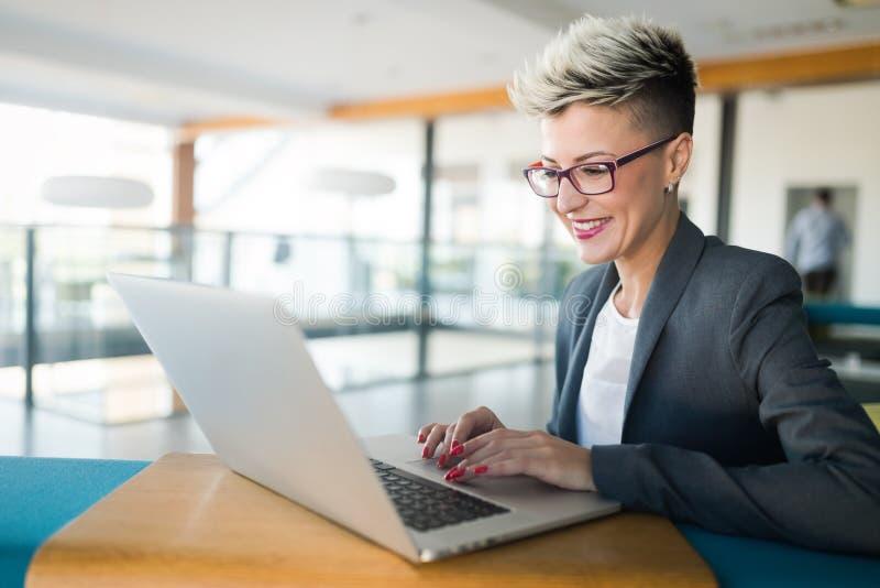 Ritratto della donna di affari che lavora al computer in ufficio fotografia stock