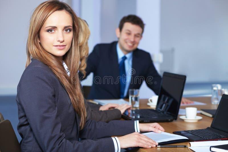 Ritratto della donna di affari che si siede alla tabella immagini stock libere da diritti
