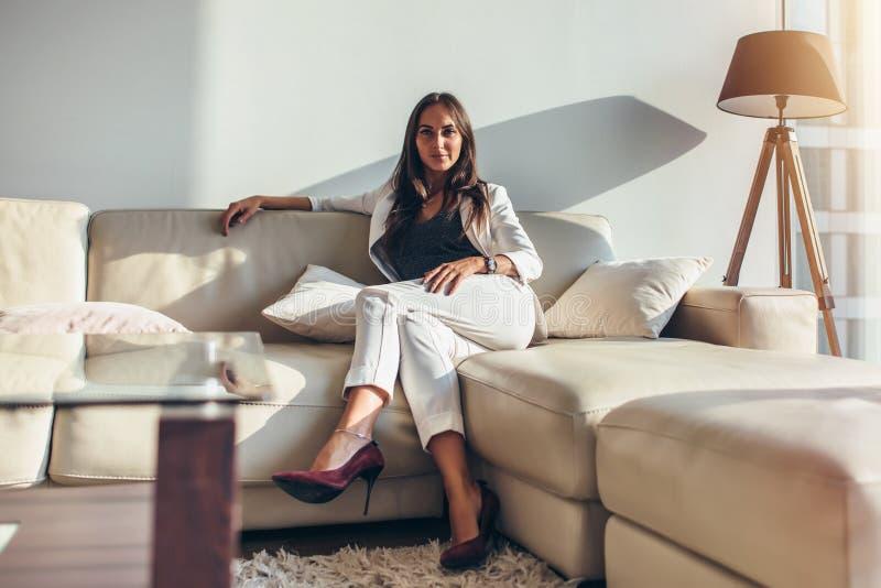 Ritratto della donna di affari che si siede sul sofà che si rilassa dopo il lavoro a casa fotografia stock libera da diritti