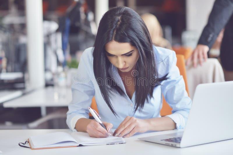 Ritratto della donna di affari graziosa che lavora nell'ufficio e nei sembrare occupati mentre facendo una nota sul taccuino fotografia stock