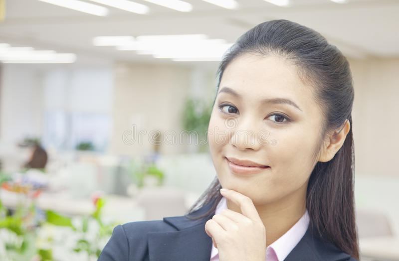 Ritratto della donna di affari sicura con la mano sul suo mento, esaminante macchina fotografica fotografie stock
