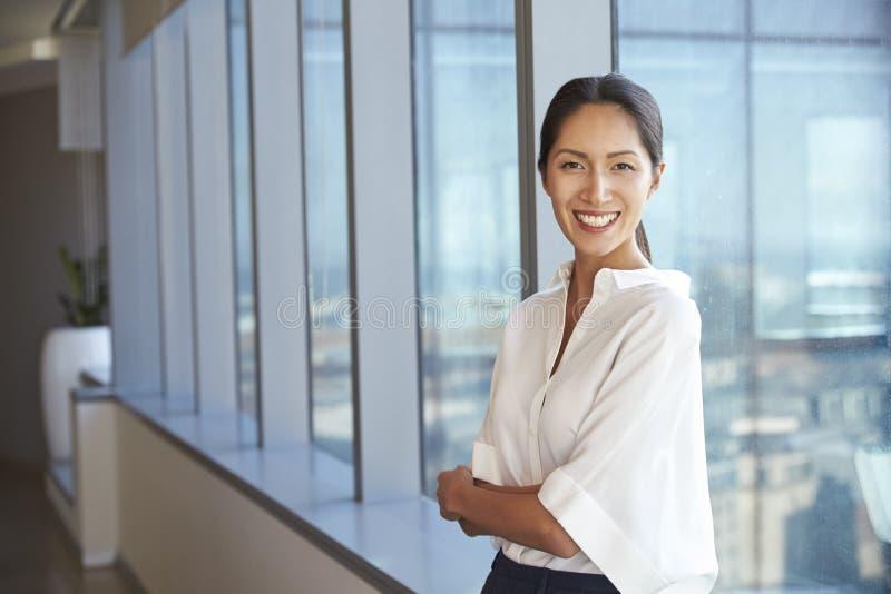 Ritratto della donna di affari Standing By Window in ufficio immagini stock