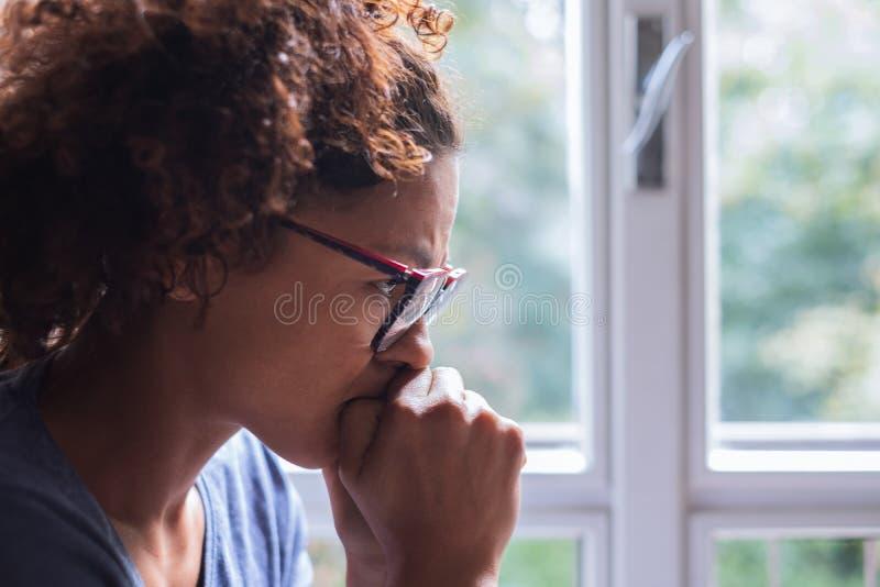 Ritratto della donna di colore pensierosa che sta accanto alla finestra fotografia stock