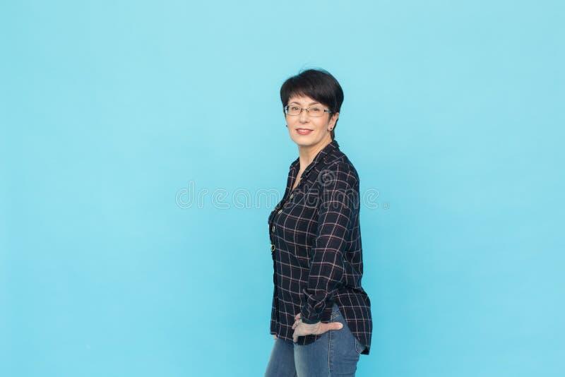 Ritratto della donna di mezza età con i vetri d'uso dei capelli di scarsità che stanno contro il fondo blu con lo spazio della co fotografia stock