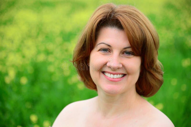 Ritratto della donna di mezza età sorridente con le spalle nude fotografia stock