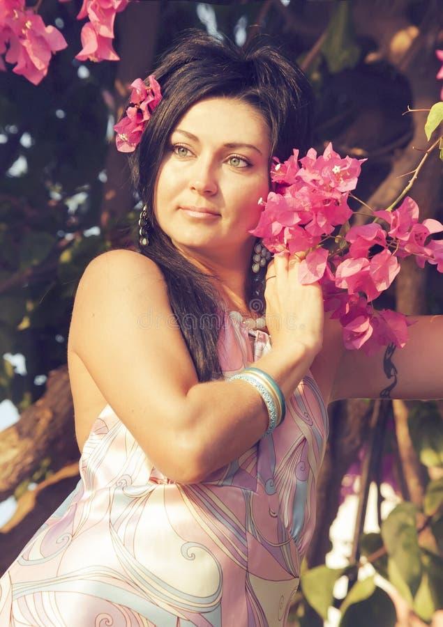 Ritratto della donna di rilassamento con i fiori rosa fotografia stock libera da diritti