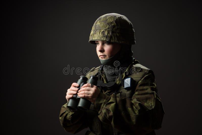 Ritratto della donna disarmata con cammuffamento Il giovane soldato femminile osserva con il binocolo fotografie stock