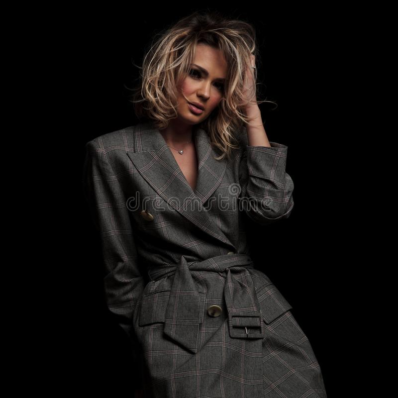 Ritratto della donna elegante che sistema i suoi capelli biondi immagine stock libera da diritti