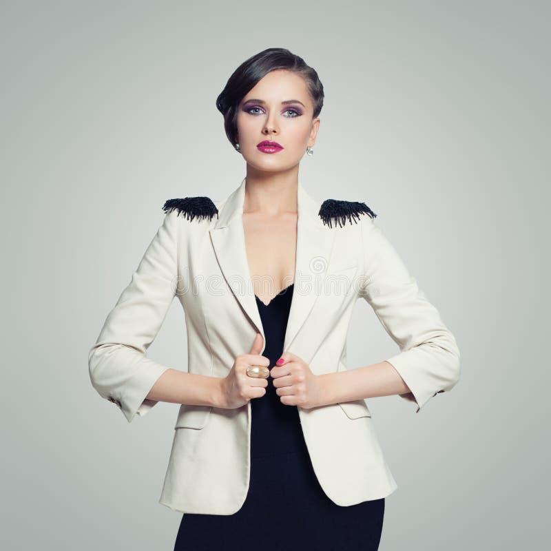 Ritratto della donna elegante del modello di moda in vestito nero sul fondo bianco della parete fotografia stock libera da diritti